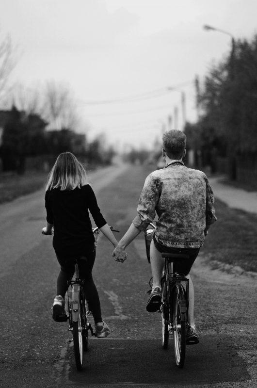 Woman and Man riding away on bikes side by side while holding hands