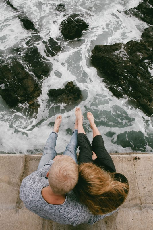Couple Sitting Over Ocean
